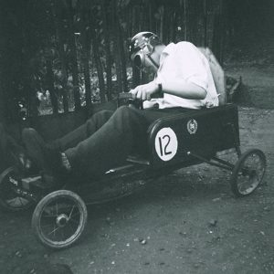 Repaired negative scan of man in go-cart