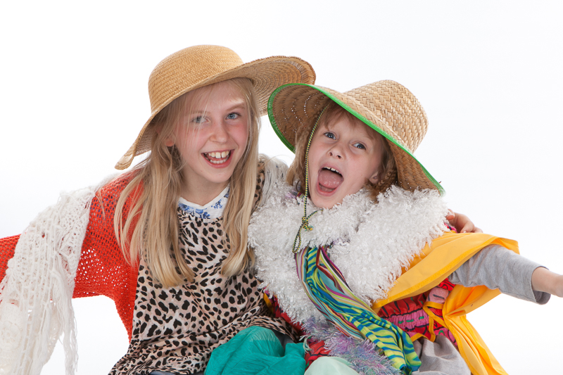 Girls having fun in hats and scarves at photoshoot party