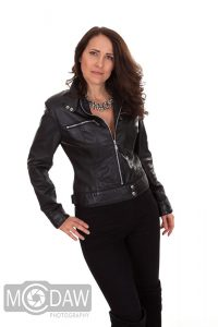 Girl in in leather jacket and trousers showing how to pose in photograph
