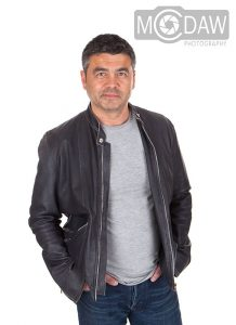 Man in leather jacket and jeans on how to pose in photograph